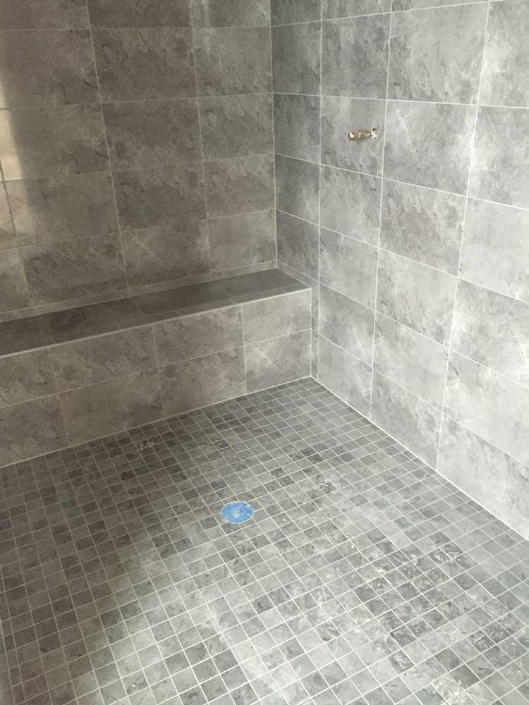 tiled walk in shower with bench using fiberglass shower pan